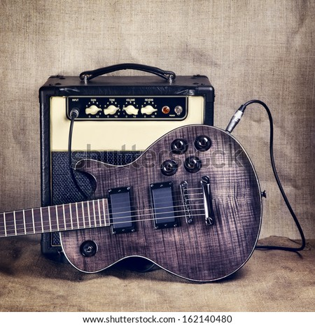 black electric guitar and amplifier on brown canvas background - stock photo