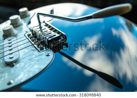 Black electric guitar and clouds. Focus point is on the front of bridge.  - stock photo