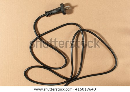 Black electrical plug and electrical cord isolated on cardboard paper. - stock photo