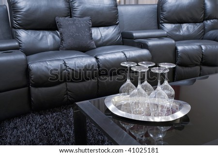 black executive leather home theater chairs with wine glasses on tray on black table