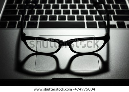 black eye glasses with shadow on laptop computer with keyboard in background low key light