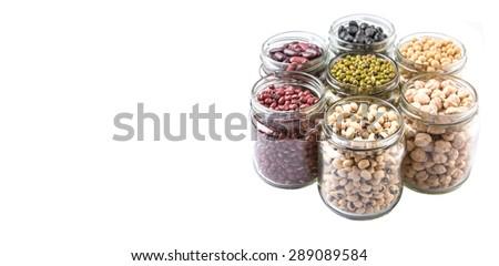 Black eye peas, chickpeas, adzuki beans, mung bean, soy beans, black beans and red kidney beans in mason jars over white background - stock photo