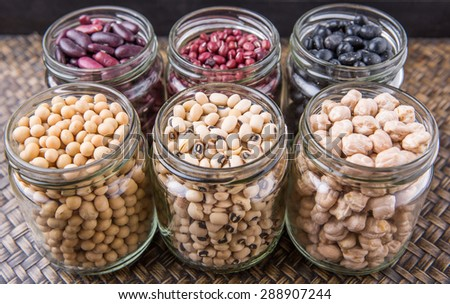 Black eye peas, chickpeas, adzuki beans, soy beans, black beans and red kidney beans in mason jars on wicker tray