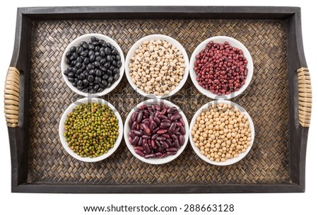 Black eye peas, mung bean, adzuki beans, soy beans, black beans and red kidney beans in white bowl on wicker tray - stock photo