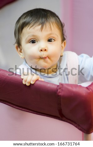 black-eyed little baby in a playpen standing and looking and kissing at camera. - stock photo