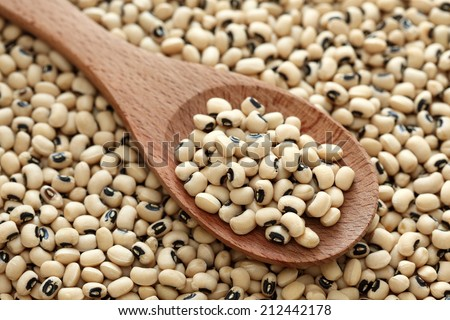 Black eyed peas in a wooden spoon on a black eyed peas background. Close-up. - stock photo