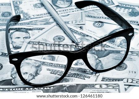 black eyeglasses and pen on a pile of dollar bills - stock photo