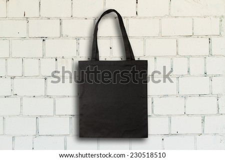 Black fabric bag against vintage brick wall - stock photo