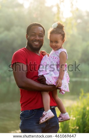 Black father hugging baby daughter at sunset. Happy family concept.