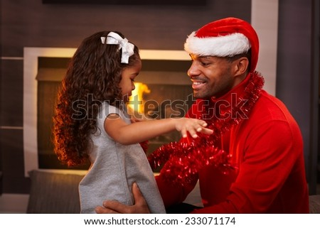 Black father in santa hat and little daughter hugging at home at christmas time. - stock photo