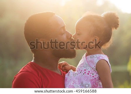 Black father kissing baby daughter at sunset. Happy family concept.