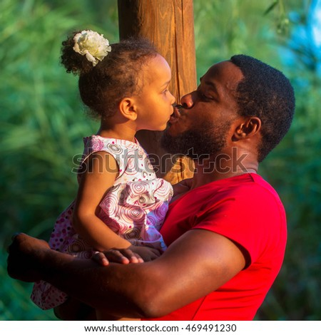Black father kissing baby daughter. Happy family concept.