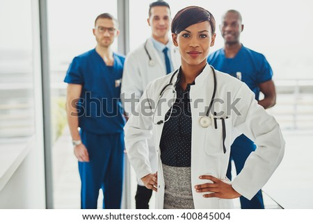 Black female doctor in charge at hospital, leading medical team om doctors and surgeons - stock photo