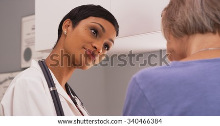 Black female radiologist discussing x-ray results with mature fe