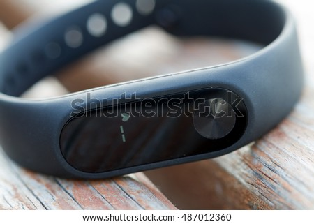 Black fitness watch with heart rate on the display. Fitness tracker on the wooden surface. Closeup.