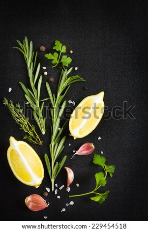 Black food background with fresh aromatic herbs and spices, top view - stock photo