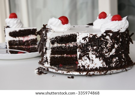 Black forest cake decorated with whipped cream and cherries. Isolated on white background. piece of cake. Girl cutting a cake for Christmas. Christmas cake - stock photo