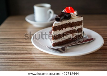 Black forest cake on wood table and coffee background  - stock photo