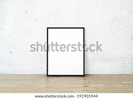 Black frame on wooden floor in concrete interior - stock photo