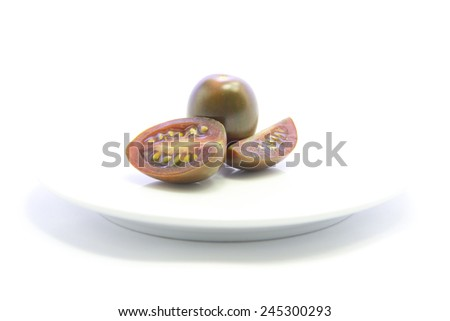 Black fresh tomato half sliced with raw on white plate and white background