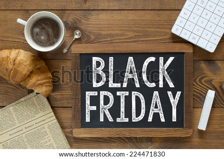 Black Friday handwritten with white chalk on a blackboard on a wooden background
