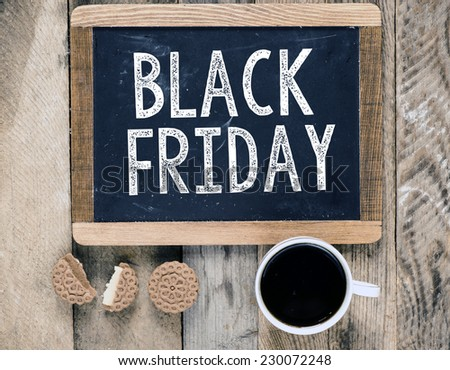 Black Friday handwritten with white chalk on a blackboard on a wooden background  - stock photo