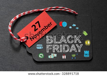 Black Friday November 27 text on a black tag with a red and white twine - stock photo