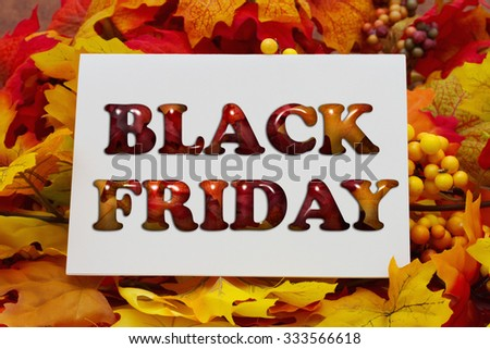 Black Friday Shopping, Autumn Leaves with a white greeting card with text Black Friday - stock photo