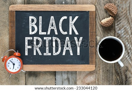 Black friday sign on blackboard with cup of coffee ,cookie and clock on wooden background - stock photo