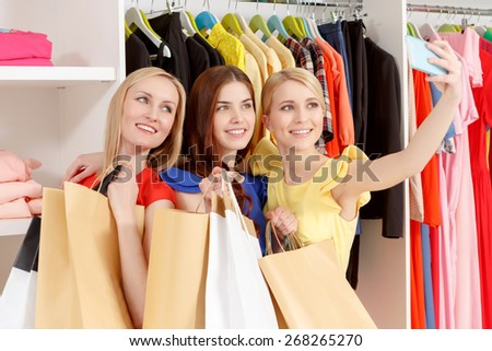 Black Friday. Three female shoppers smiling happily to the camera of their phone holding numerous paper bags in a fashion store - stock photo
