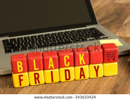 Black Friday written on a wooden cube in a office desk - stock photo
