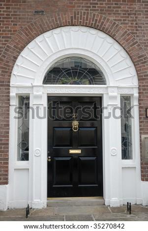 Black front door in urban street - stock photo