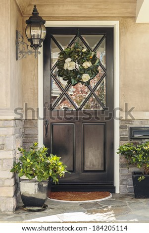 Black front door to home with flower wreath. A black front door to a home with an ornate flower wreath and classic light fixture. Also seen are door plants, and a stone porch.  - stock photo