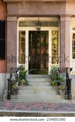 Black Front Door with Surrounding Windows and White Door Frame  - stock photo