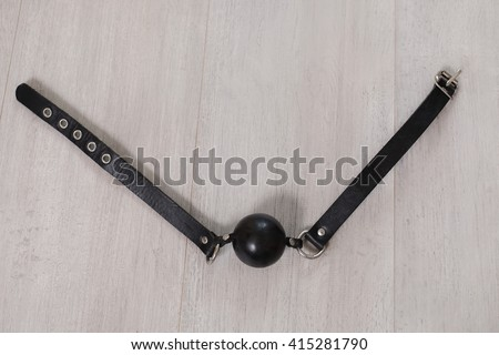 black gag on the wooden floor,  barnacle, sex toys, BDSM toys, fetish toys, role-playing games, sexual fetishism, sexual conduct   - stock photo