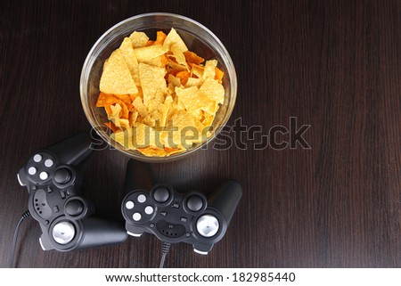 Black game controllers and bowl with snacks on wooden background - stock photo