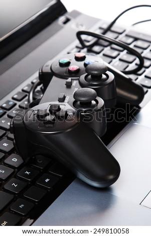 Black gamepad is lying on a laptop keyboard - stock photo