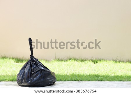 Black garbage bag on grass field and wall background. - stock photo