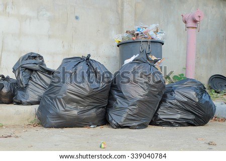 Black garbage bags on the street beside the concrete wall and fire hydrant - stock photo