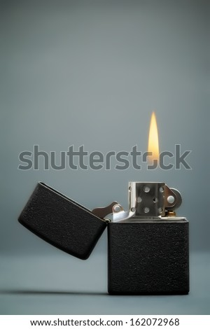 black gasoline lighter with flame on dark background - stock photo
