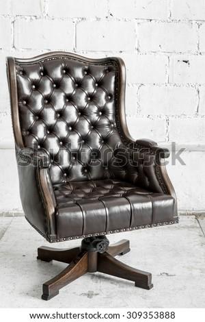 Black genuine leather classical style sofa in vintage room - stock photo