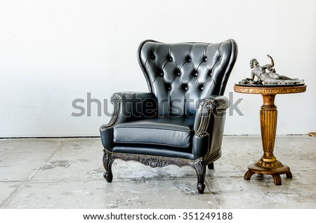 Black genuine leather classical style sofa in vintage room with desk - stock photo