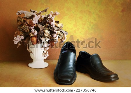 Black genuine shoes on grunge with dry flowers in vase still life art photography - stock photo