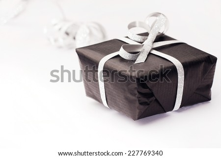 Black gift box with silver bow on light background. - stock photo