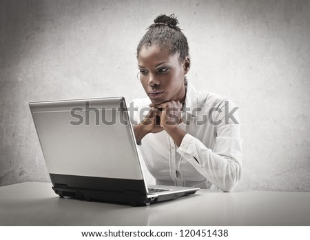 Black girl waiting for an answer in front of a laptop computer - stock photo