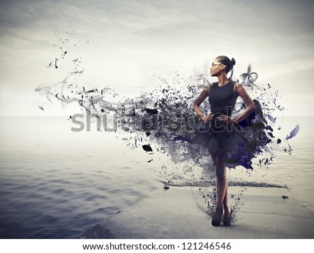 Black girl, with a black dress which becomes paint, standing on a pier