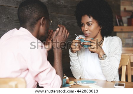 Black girl with Afro hairstyle holding a cup of coffee, listening and looking at her boyfriend with amorous expression. Loving couple enjoying time together at a restaurant on Saint Valentine's Day - stock photo