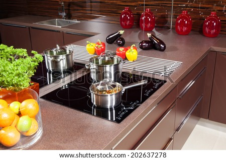 Black glass induction hob in the kitchen - stock photo
