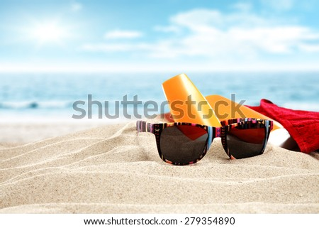 black glasses and sand