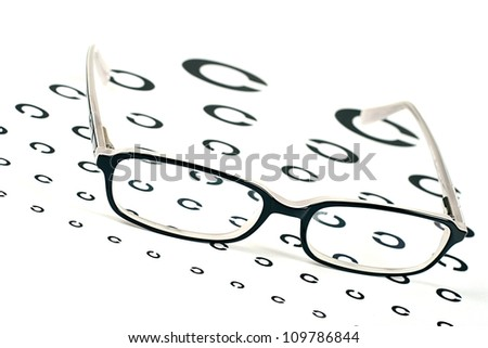 black glasses on a eyesight test chart - stock photo